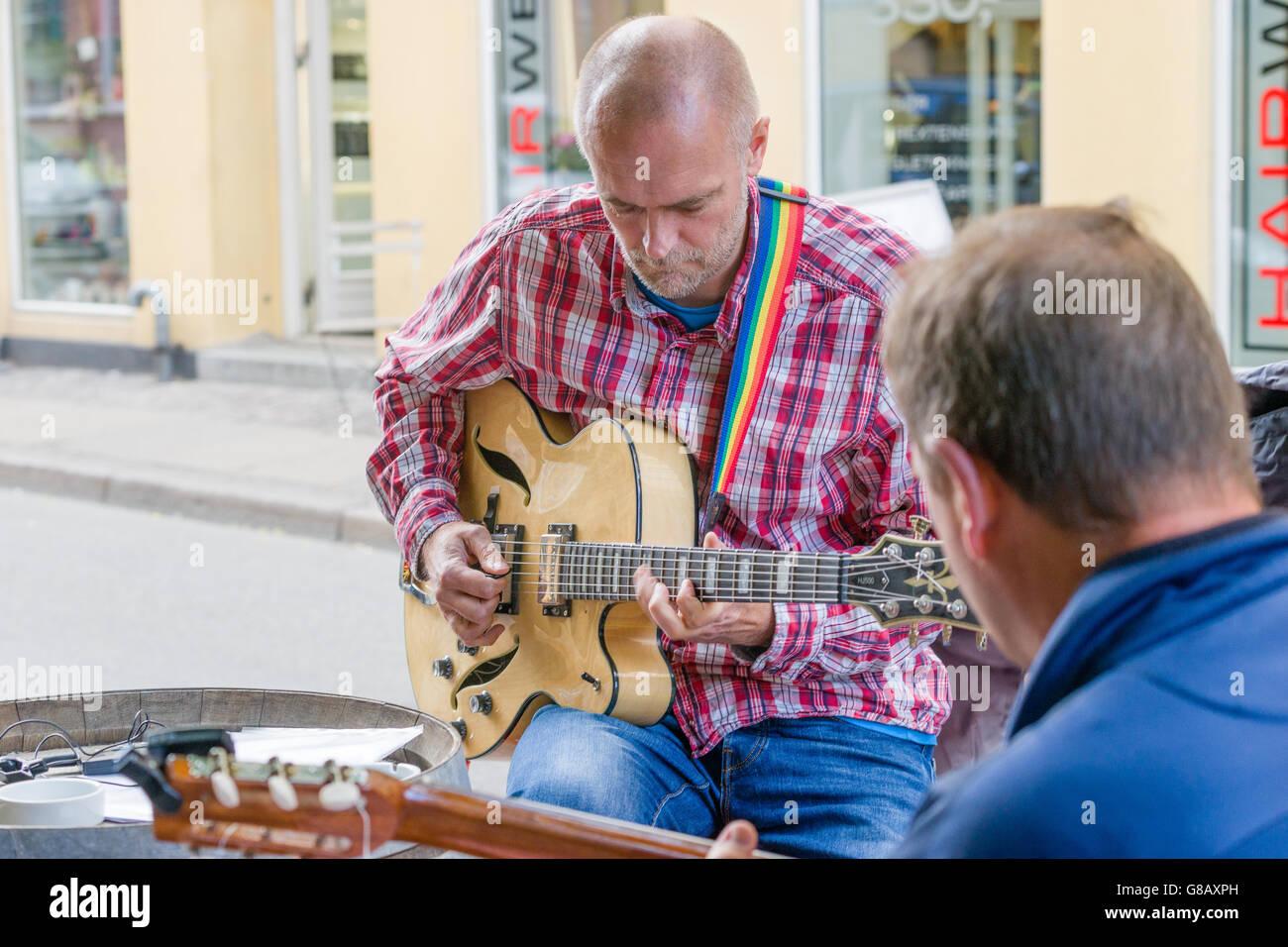 Jazz guitar street music between people and bicycles in Copenhagen, two men playing - Stock Image