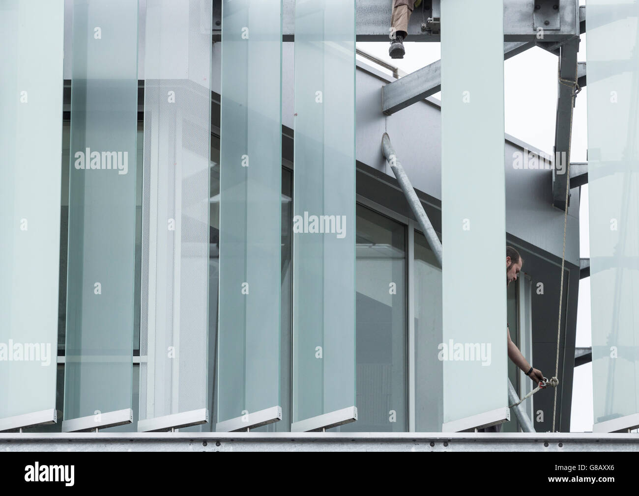 Workmen fitting external glass louvres on energy efficient new office block in Spain Stock Photo