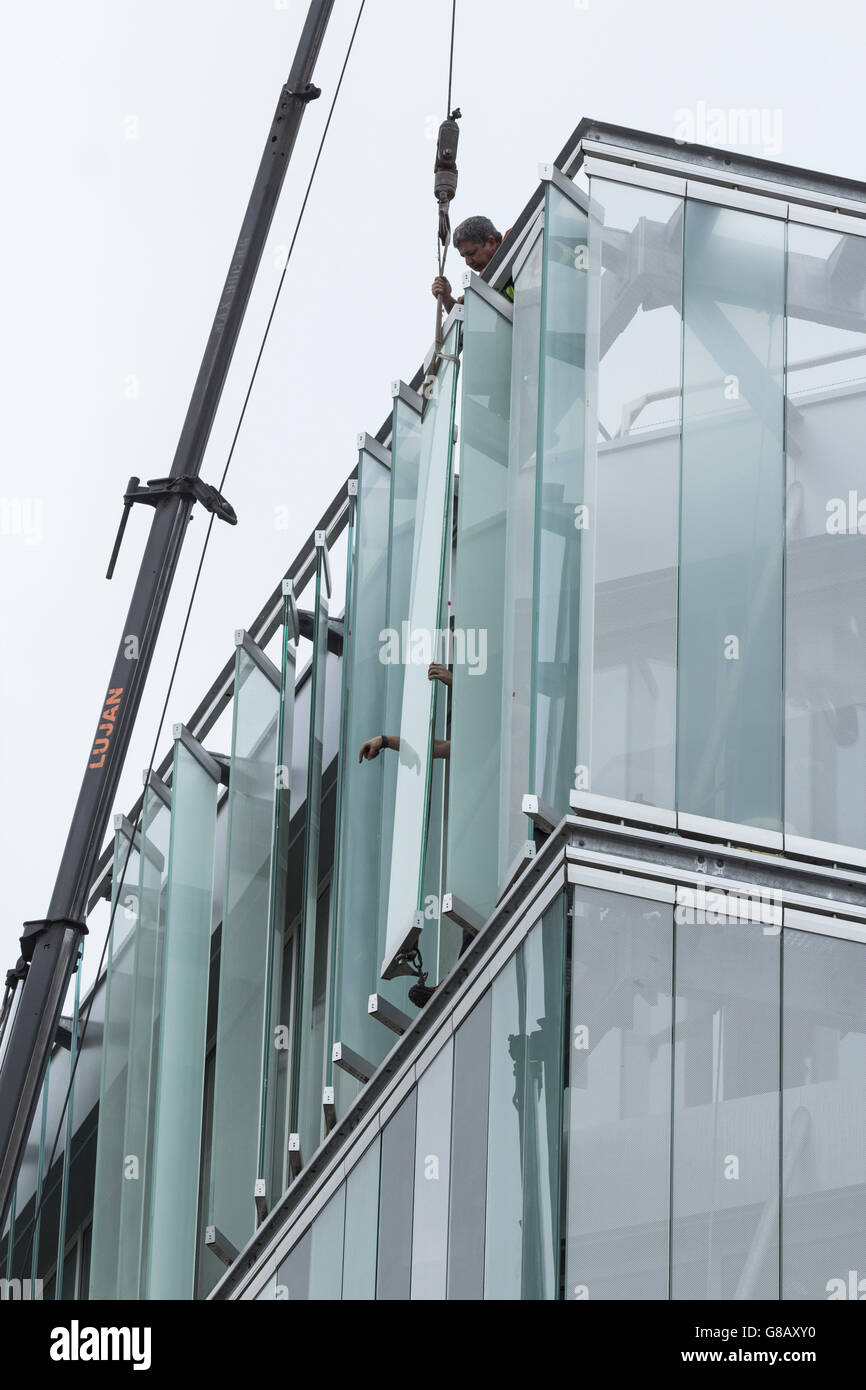 Workmen fitting external glass louvres on energy efficient new office block in Spain - Stock Image