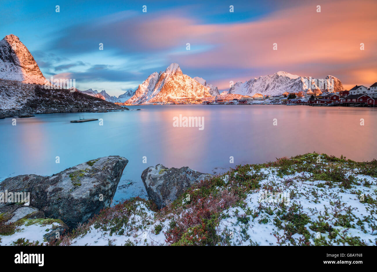 The pink sky at sunrise illuminates Reine village with its cold sea and the snowy peaks Lofoten Islands Northern - Stock Image
