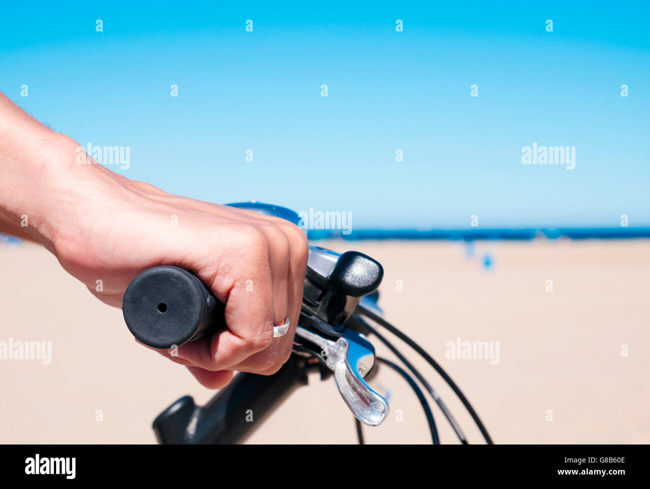 closeup of a young caucasian man riding a bicycle by the seafront, with the ocean in the background - Stock Image
