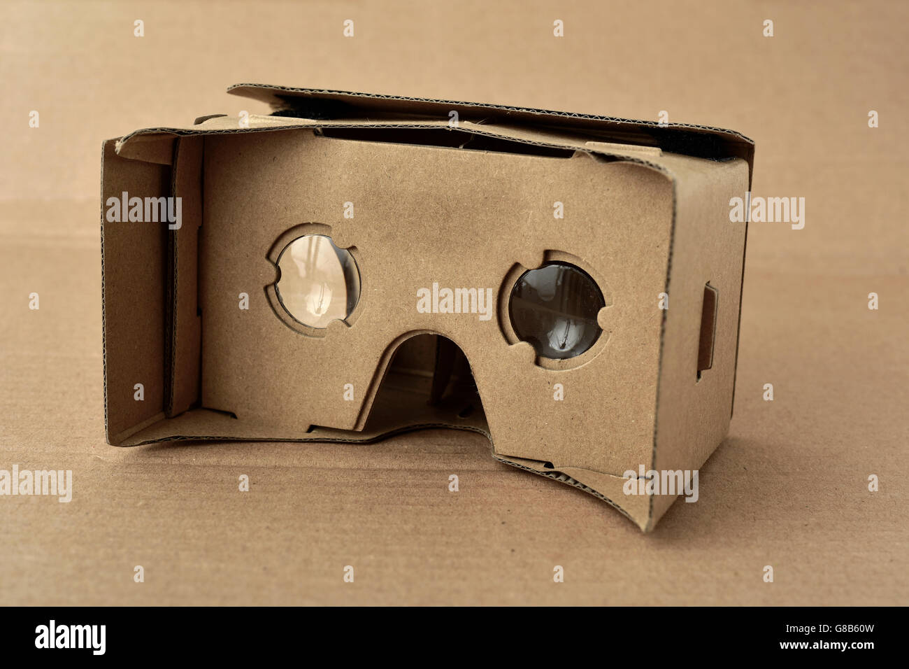 closeup of a pair cardboard virtual reality lenses on a cardboard background - Stock Image