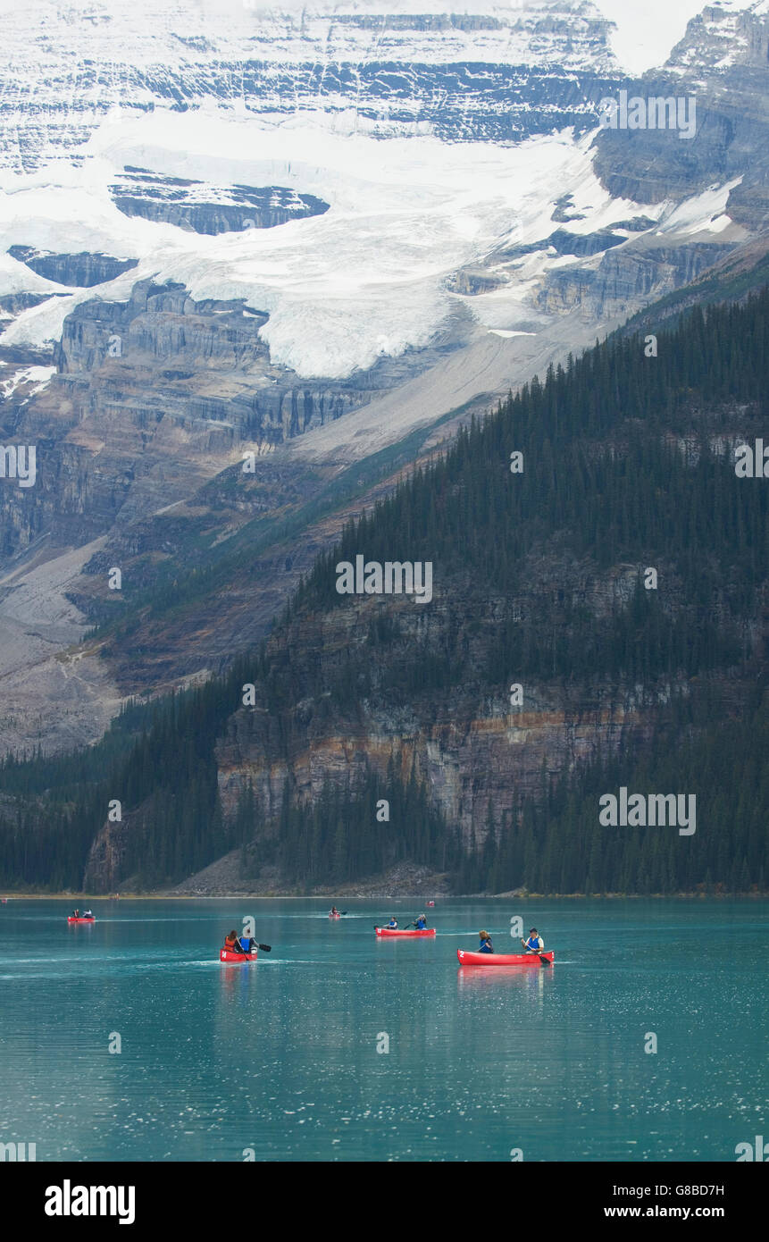 Canoeists paddling red canoes on Lake Louise, Banff National Park - Stock Image