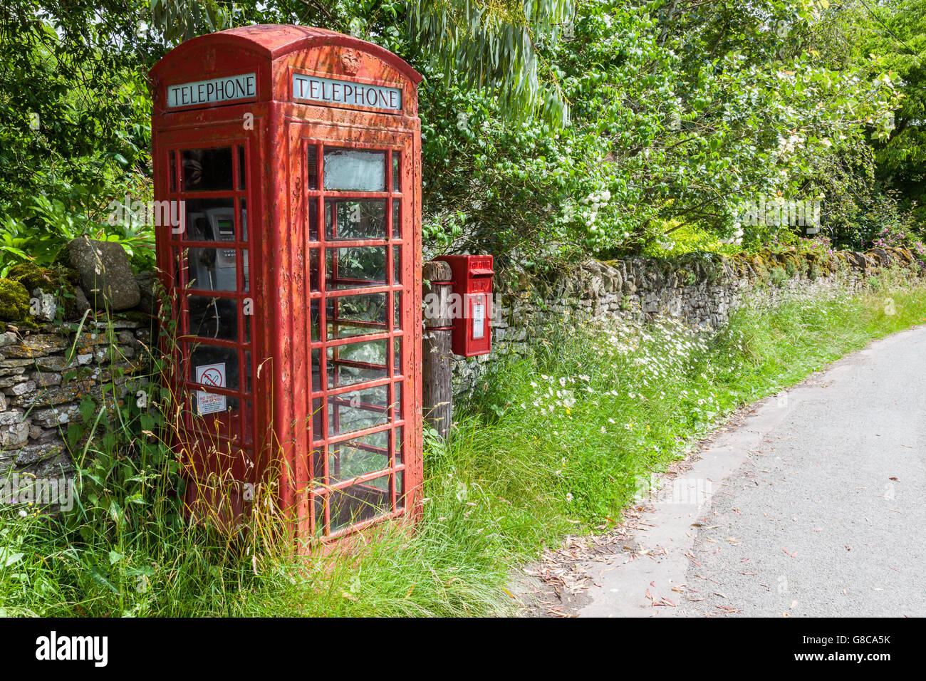 Red telephone box and red postbox in the village of Norbury, Shropshire, England, UK - Stock Image