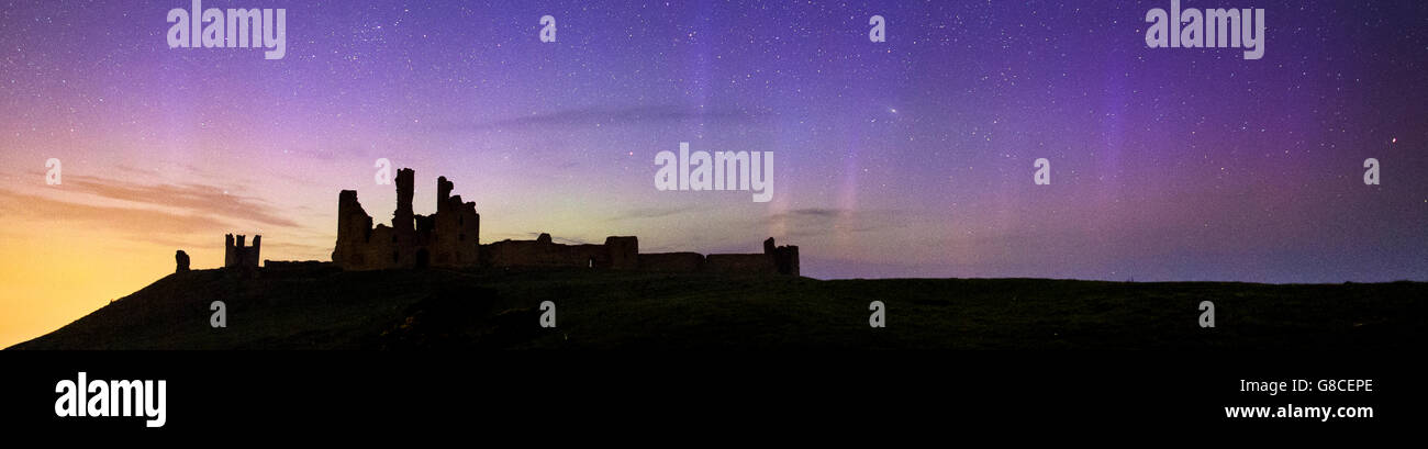 The Northern Lights dance gently behind the ruins of Dunstanburgh Castle, Northumberland, UK - Stock Image