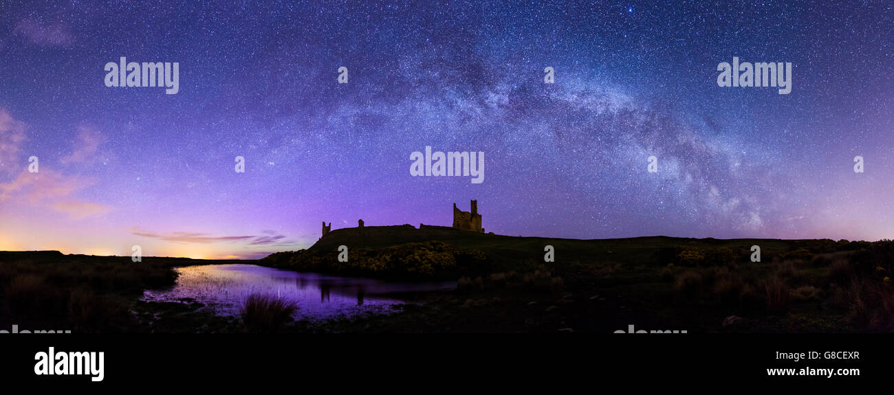 Dunstanburgh Castle with the Milky Way and Northern Lights - Stock Image