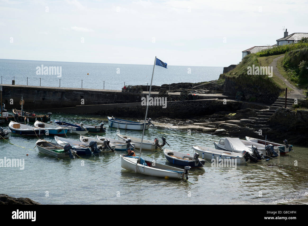 Cornwall June 2016. Port Scatho. Dingy flying a European flag, preparing to sail away on day of EU referendum - Stock Image