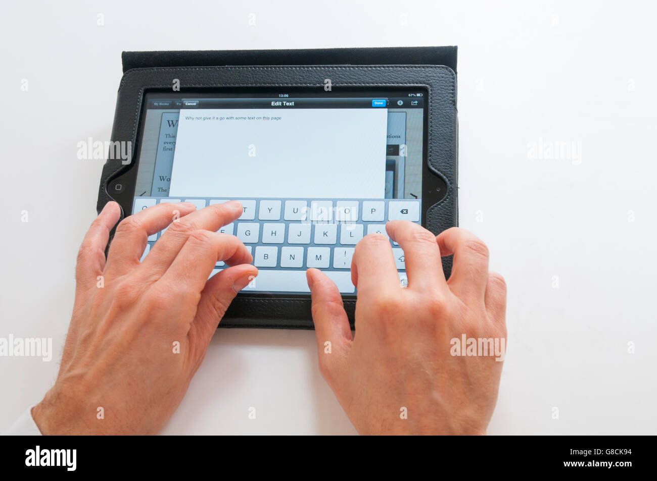 Man's hands typing on a tablet keyboard. - Stock Image