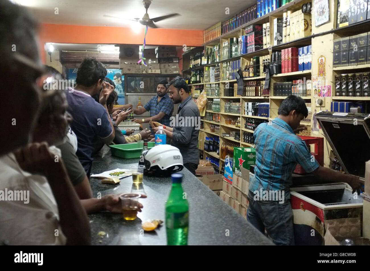 scenes from indian wine shops, a cross between a liquor store and a bar, full of local people drinking cheap branded - Stock Image