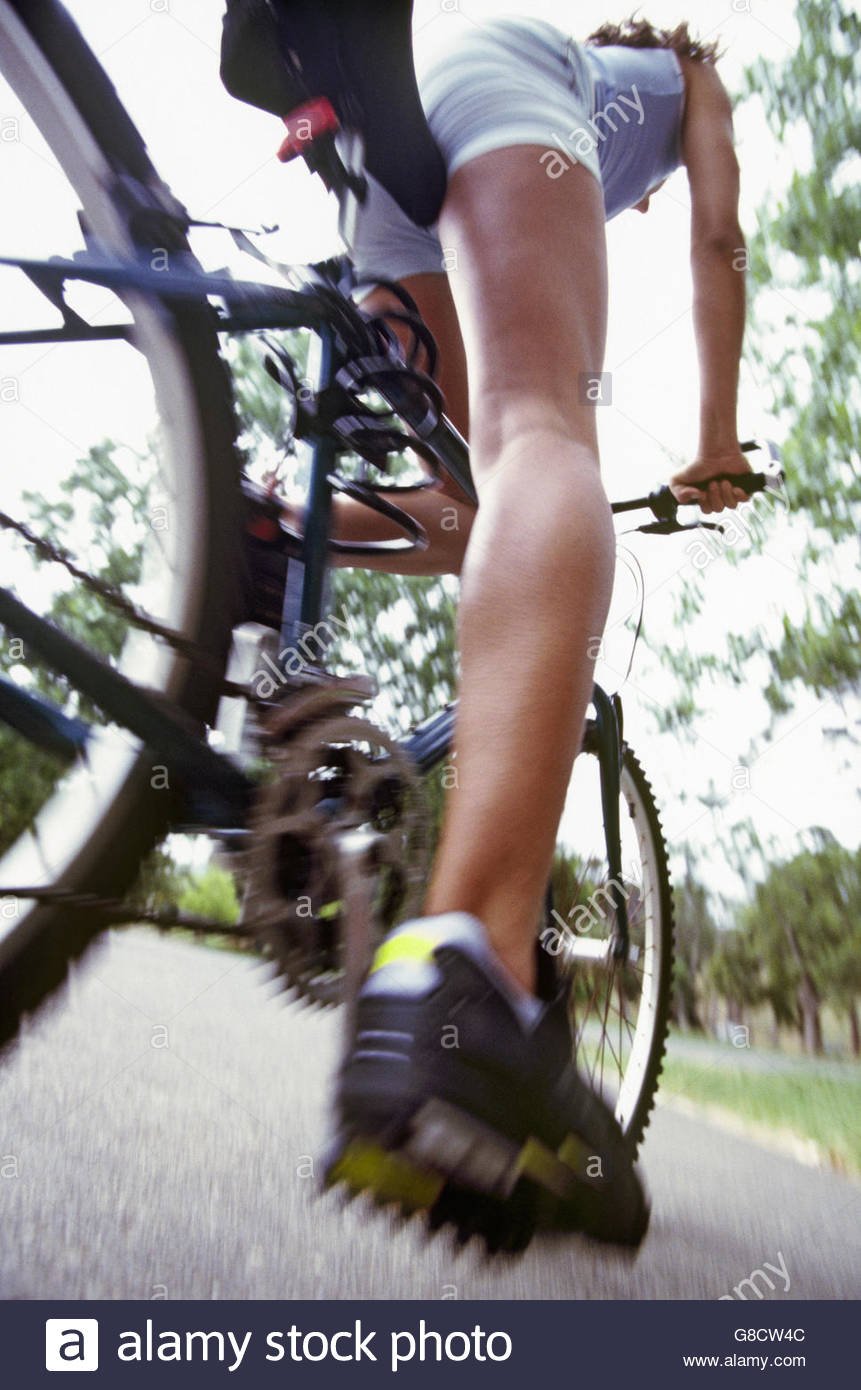 Blurred motion of woman cycling - Stock Image