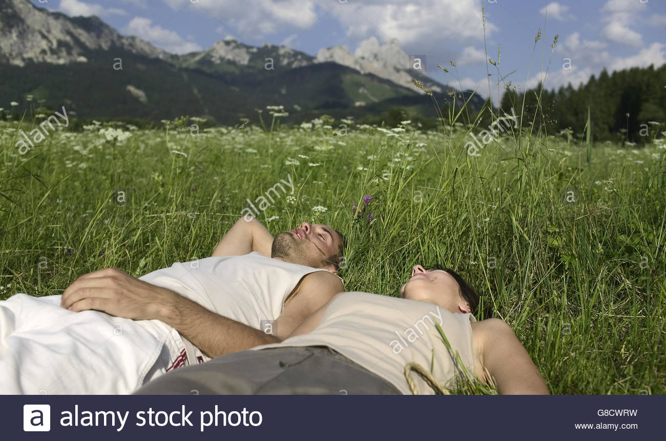 Couple lying in a field - Stock Image