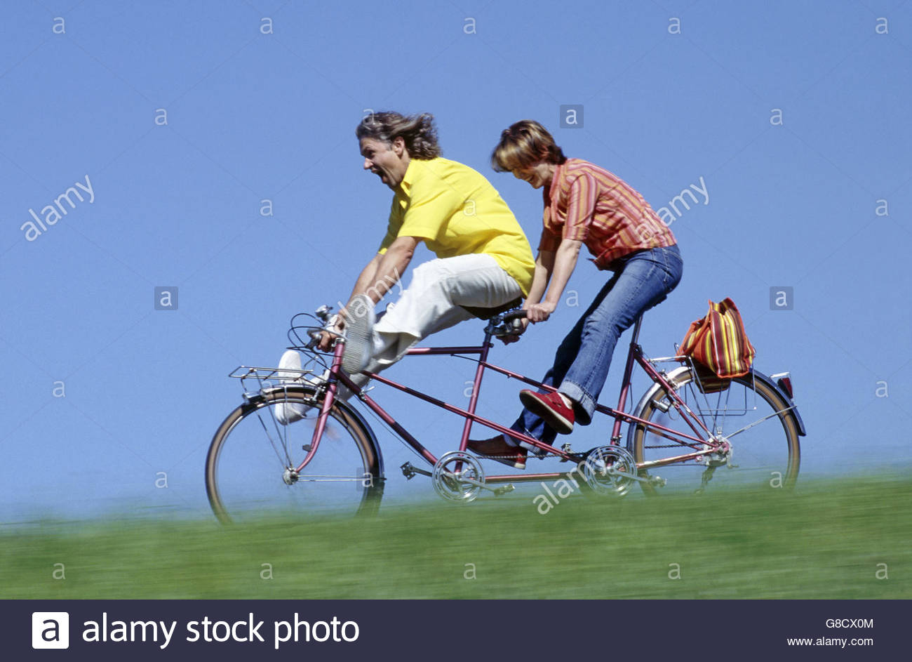Couple riding a tandem bike - Stock Image