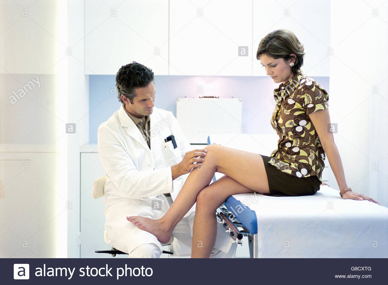 Portrait of a male doctor checking a young woman's reflexes - Stock Image