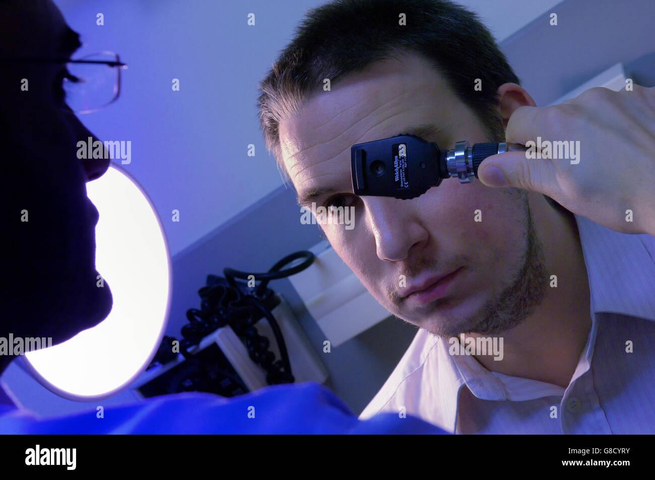 Eye examination using a Ophthalmoscope - Stock Image