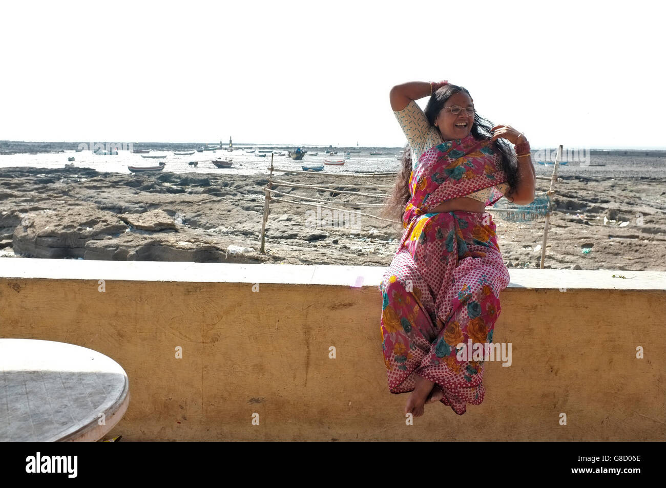 an indian local woman in saree poses at the beach front at the slum area of chimbai village, bandra, mumbai, india - Stock Image