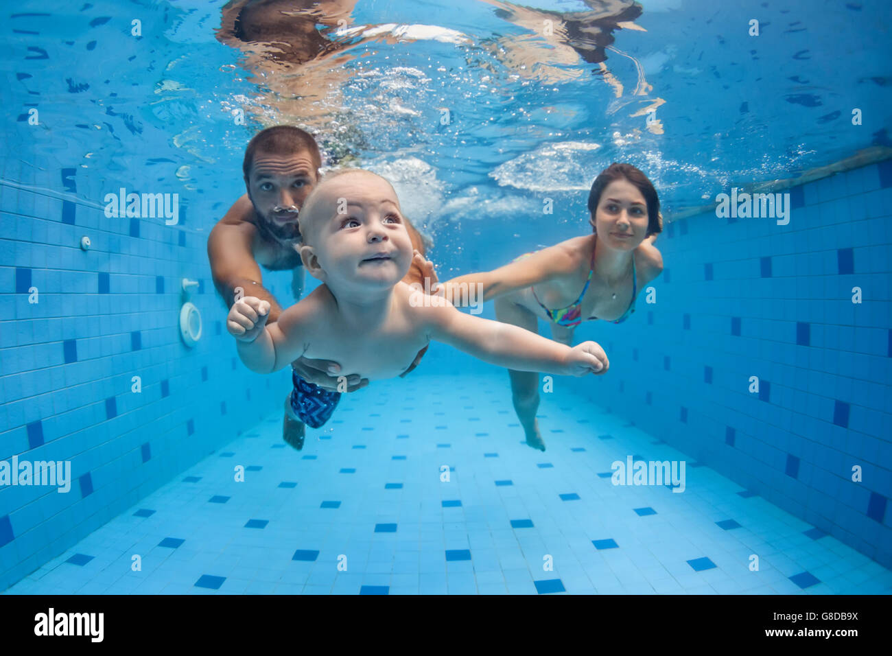 Happy full family - mother, father, baby son learn to swim, dive underwater with fun in pool to keep fit. - Stock Image