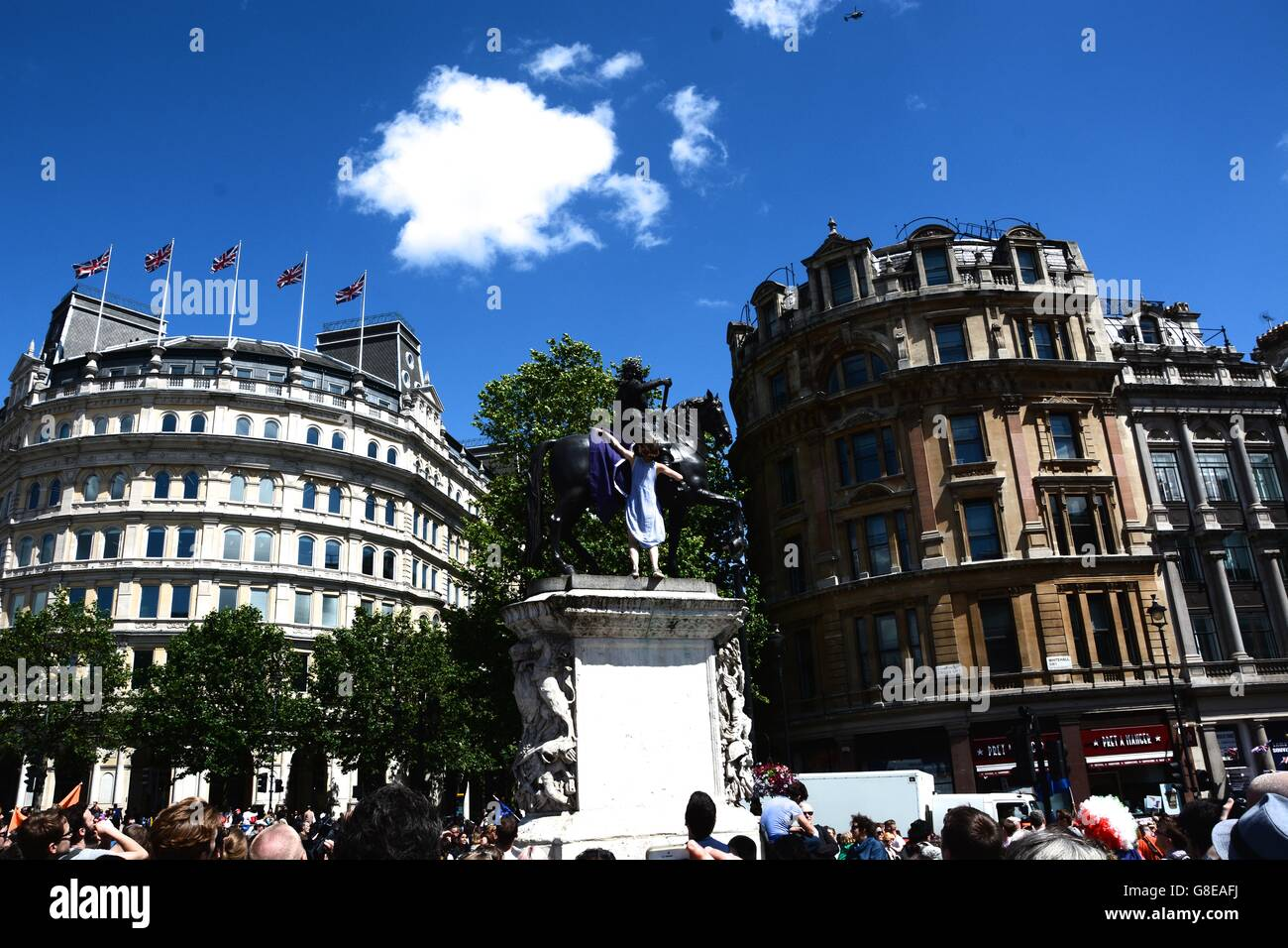 A young Pro-European demonstrator on the March for Europe climbs onto a statue in Trafalgar Square. - Stock Image