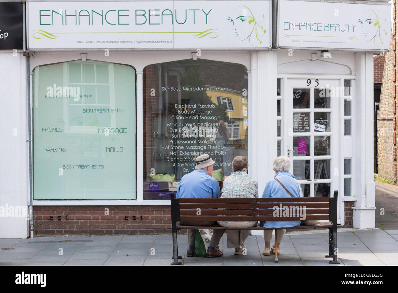 Three elderly people sitting on a bench outside a beauty parlour in Clacton UK Stock Photo