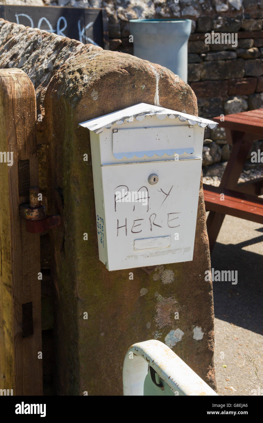 Honesty box for unsupervised payments for car parking at an unofficial car park at Pooley Bridge, Cumbria. - Stock Image
