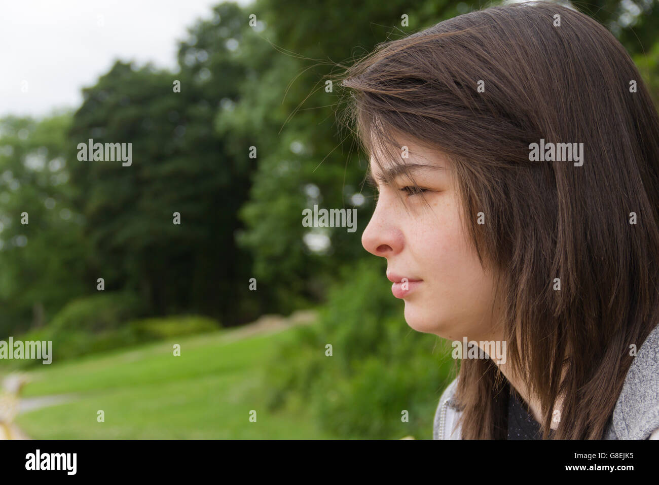 Young woman, adult or late teens, seated in park with a solemn or neutral expression on her face. - Stock Image