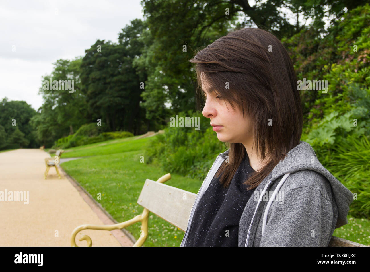 Young woman,  adult or late teens, seated in park with a solemn or slightly sad expression on her face. - Stock Image
