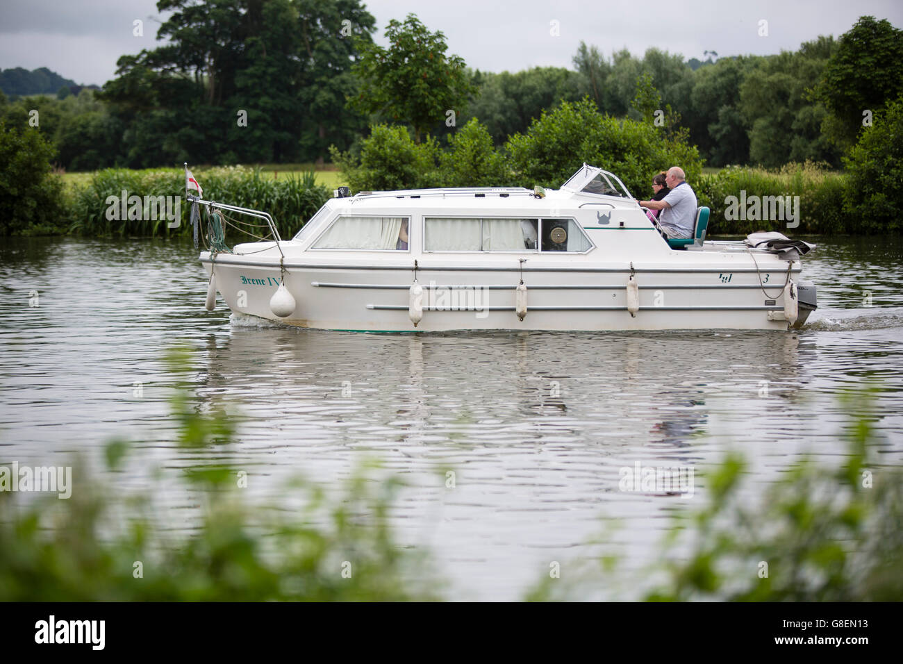 A small motor boat sailign on the river thames. - Stock Image