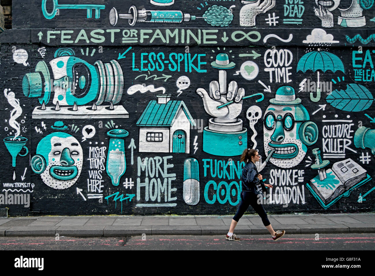 A young woman walks by a piece of street art by Italian street artist Mr. Thoms in Holywell Lane, Shoreditch, East - Stock Image