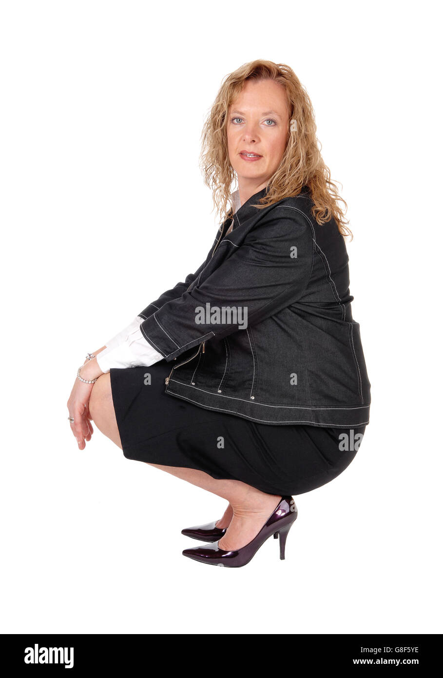 A beautiful blond woman crouching on the floor in a black skirt and navy jacket, isolated for white background. - Stock Image
