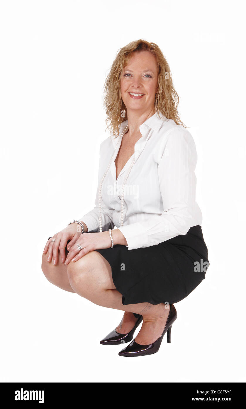 A beautiful blond woman crouching on the floor in a black skirt and white blouse, isolated for white background. - Stock Image