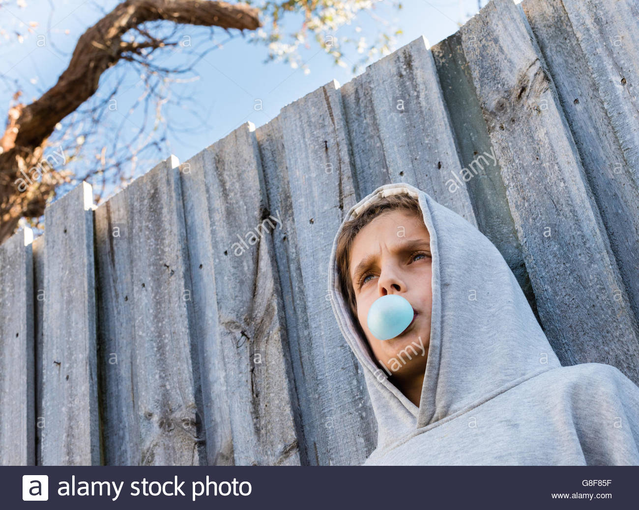 Below angled view of teenage boy in grey hoodie blowing blue bubble gum against grey wooden fence - Stock Image