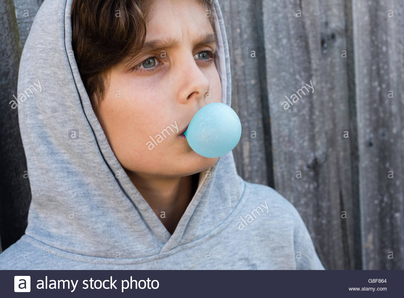 Close up angled view of teenage boy in grey hoodie blowing blue bubble gum against grey wooden fence - Stock Image