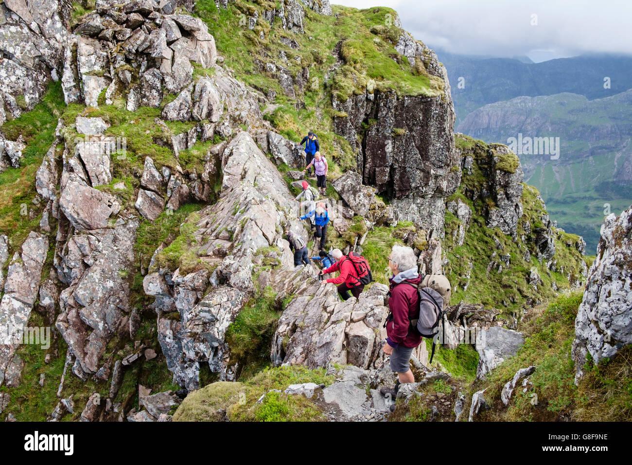 Hikers scrambling on steep rocky pinnacles of Aonach Eagach ridge. Glencoe, Highland, Scotland, UK, Britain - Stock Image