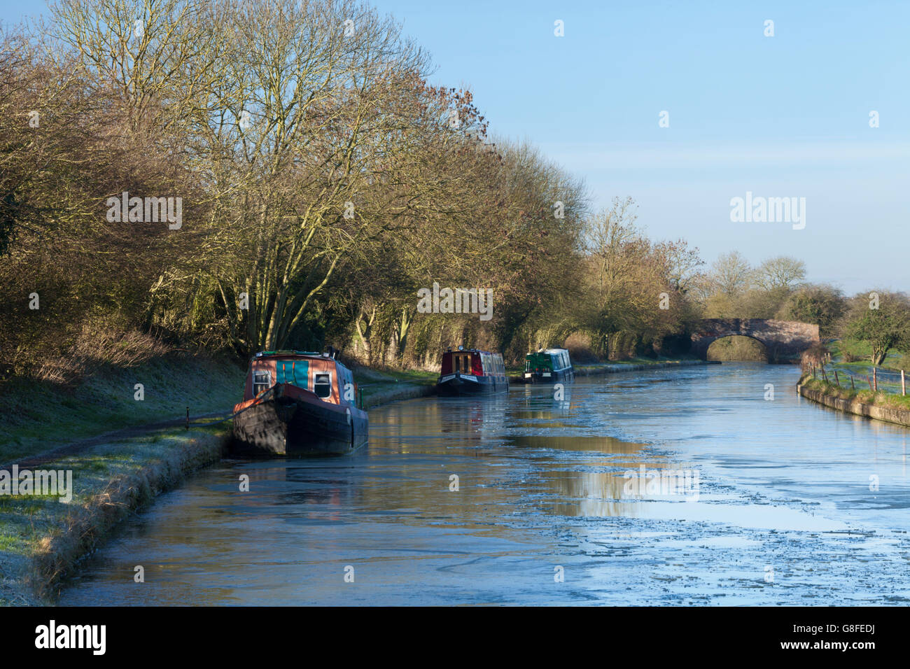 Three narrowboats moored on a frozen Grand Union canal between Norton Junction and Braunston in Northamptonshire, - Stock Image