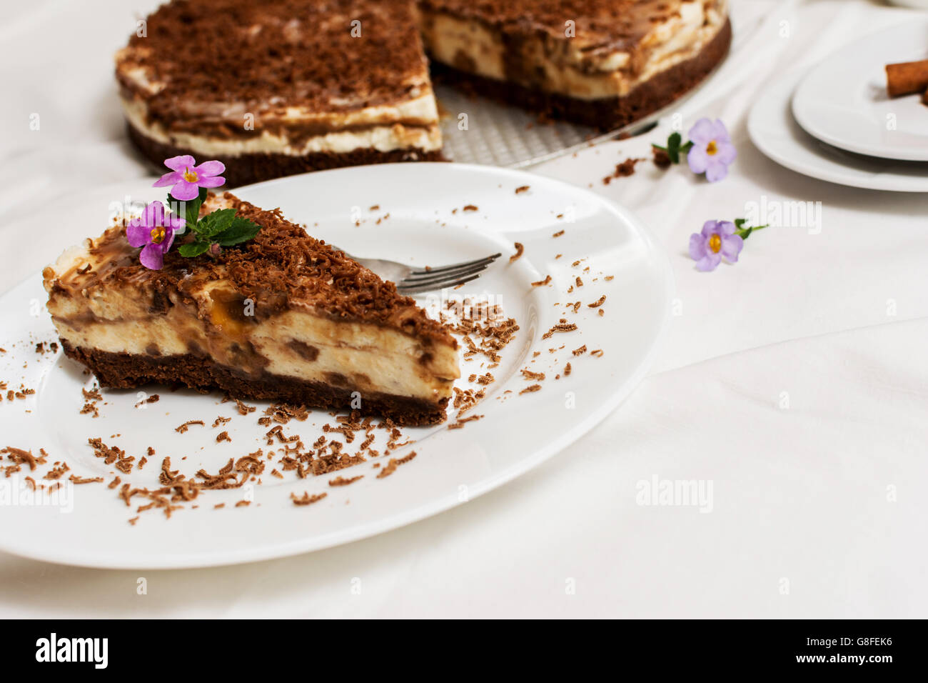 Traditional caramel cheesecake with chocolate and flower on white plate - Stock Image