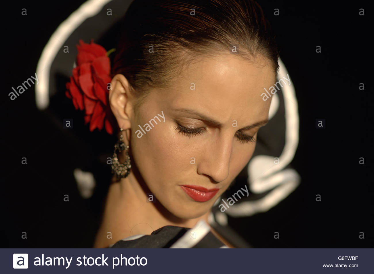 Portrait of a young woman with a flower pinned in her hair - Stock Image
