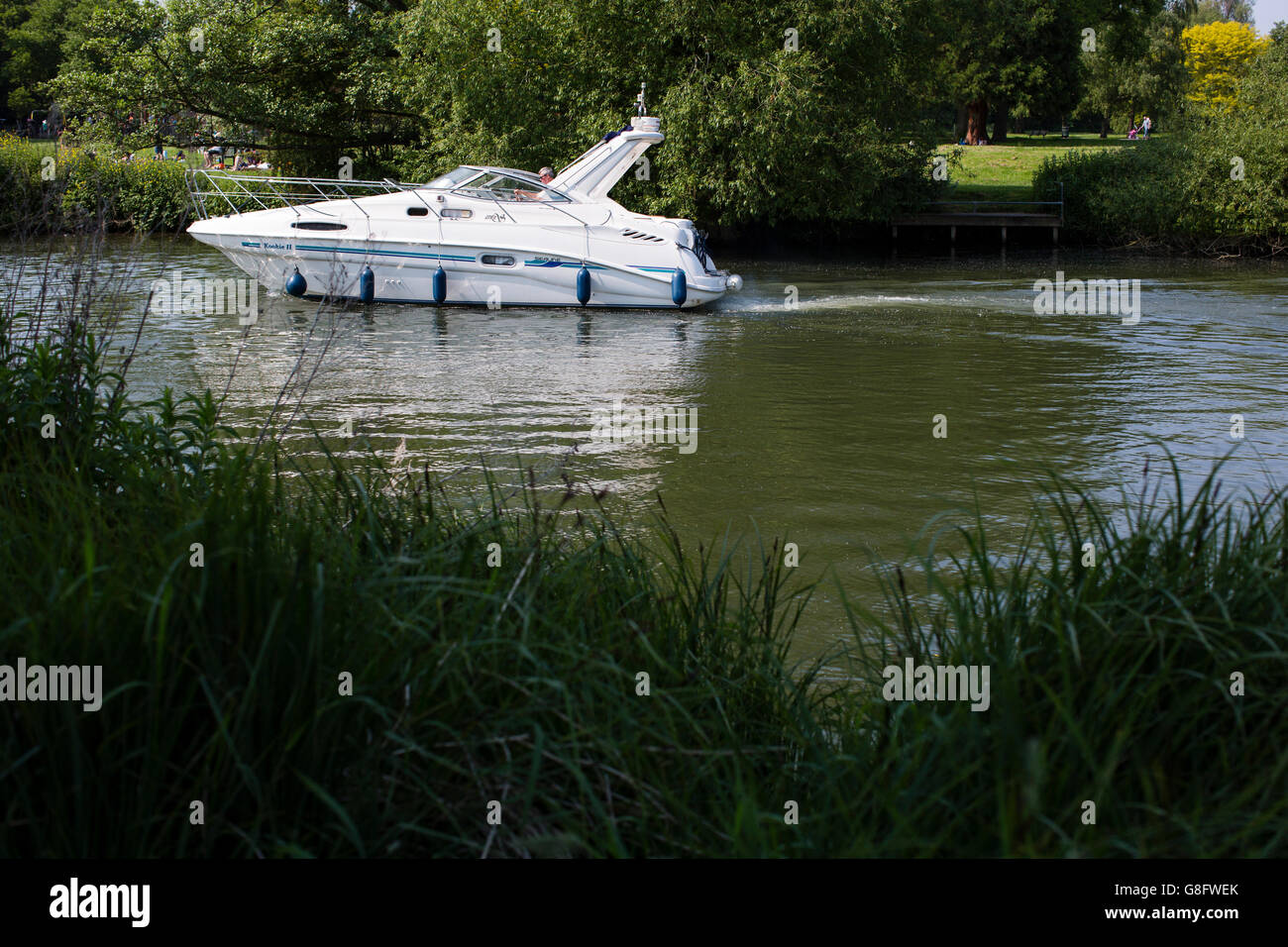 A small motor boat sailing on the river thames. - Stock Image