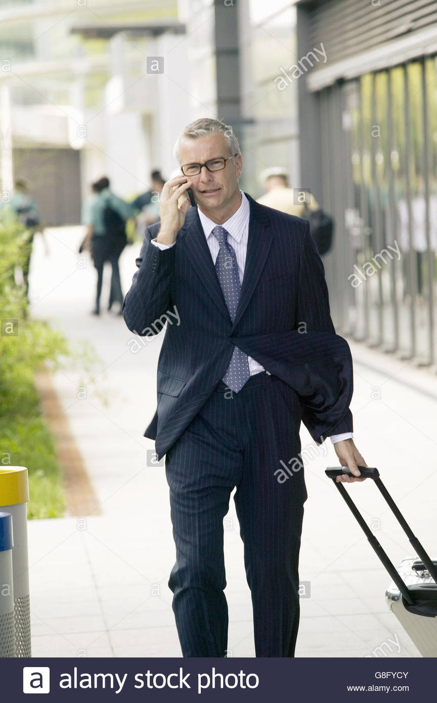 Middle-aged businessman on cell phone with suitcase - Stock Image