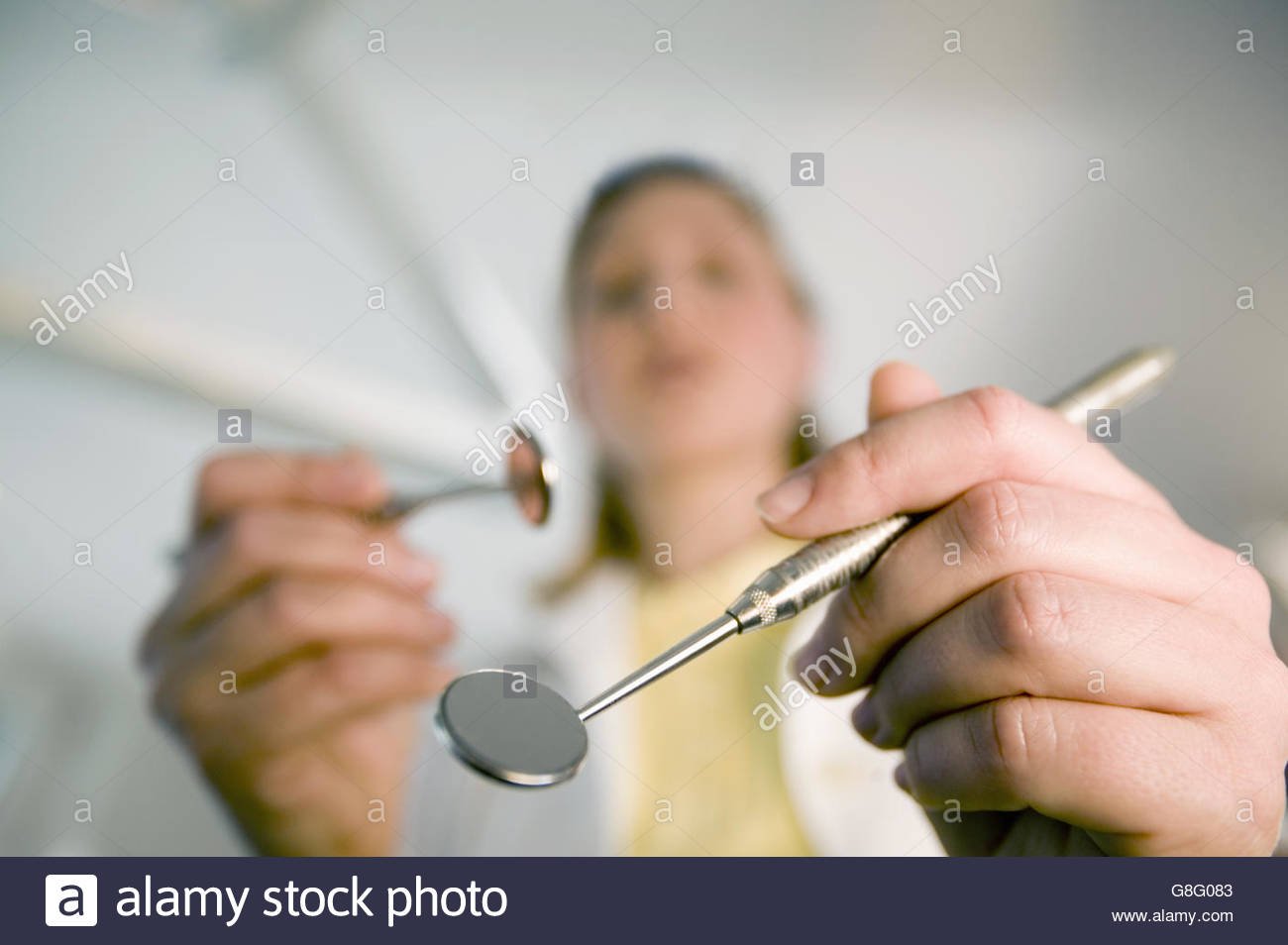 Female dental assistant holding dental mirrors - Stock Image