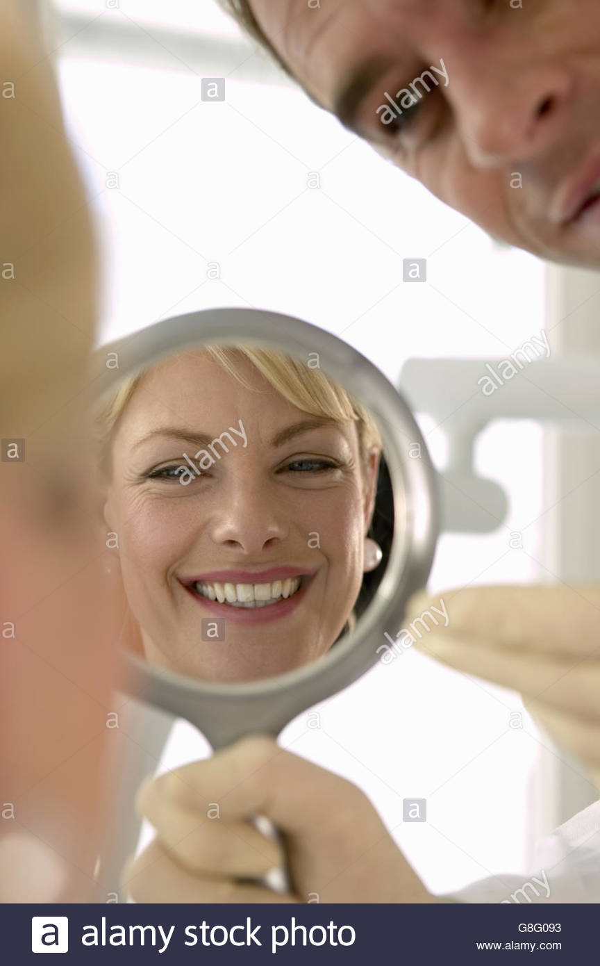 Reflection of woman smiling in mirror with dentist - Stock Image