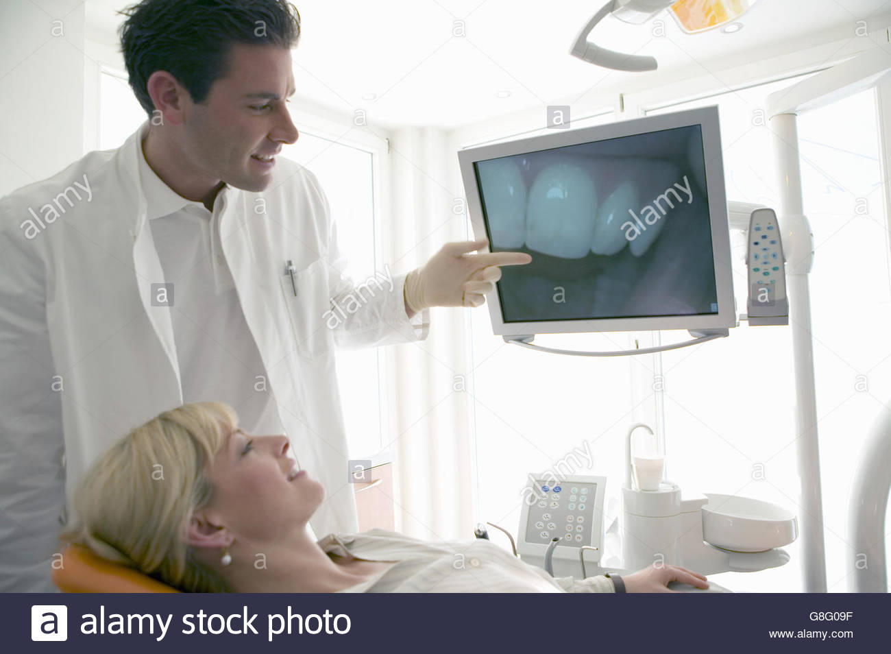 Male dentist showing patient picture of her teeth - Stock Image