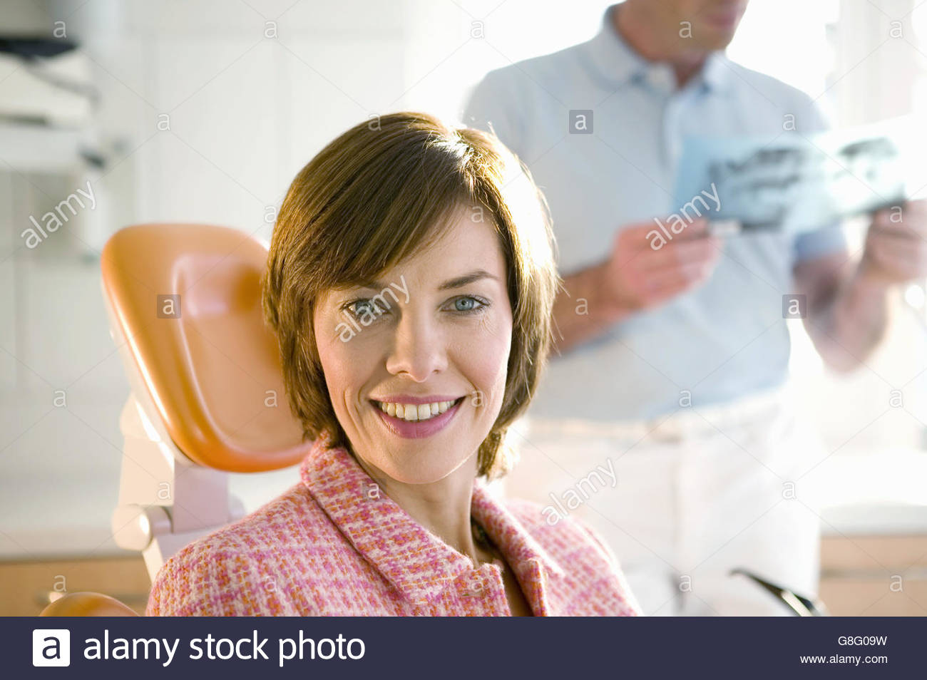 Woman smiling in dentists chair - Stock Image