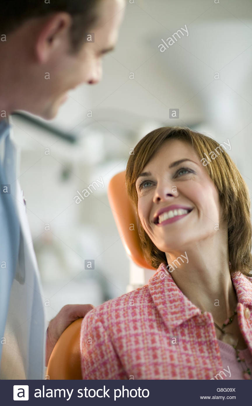 Female patient smiling at dentist - Stock Image