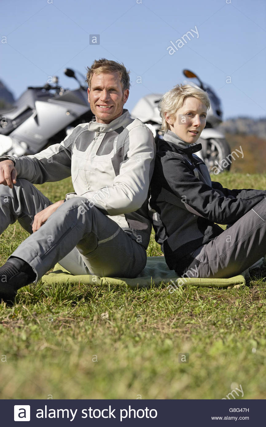 Biker couple sitting in grass next to motorcycles - Stock Image