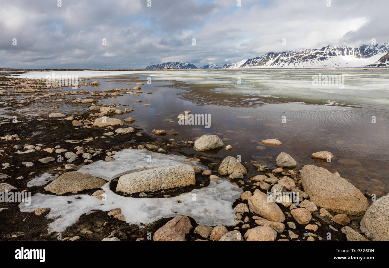 Shallow pool with melting ice and snow-capped mountains at Smeerenburg whaling site, Svalbard archipelago, Norway - Stock Image
