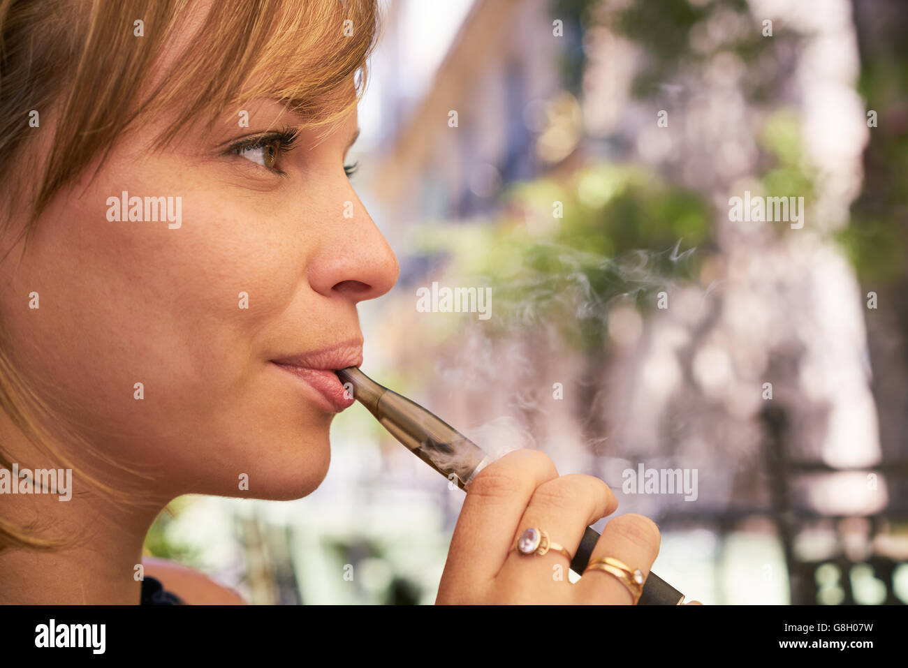 Young woman having fun and relaxing outdoors, smoking electronic cigarette e-cig. Closeup of face and copy space - Stock Image