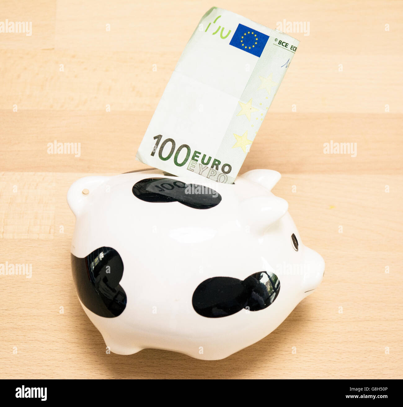 Piggy bank with hundred euros on the old wooden background - Stock Image