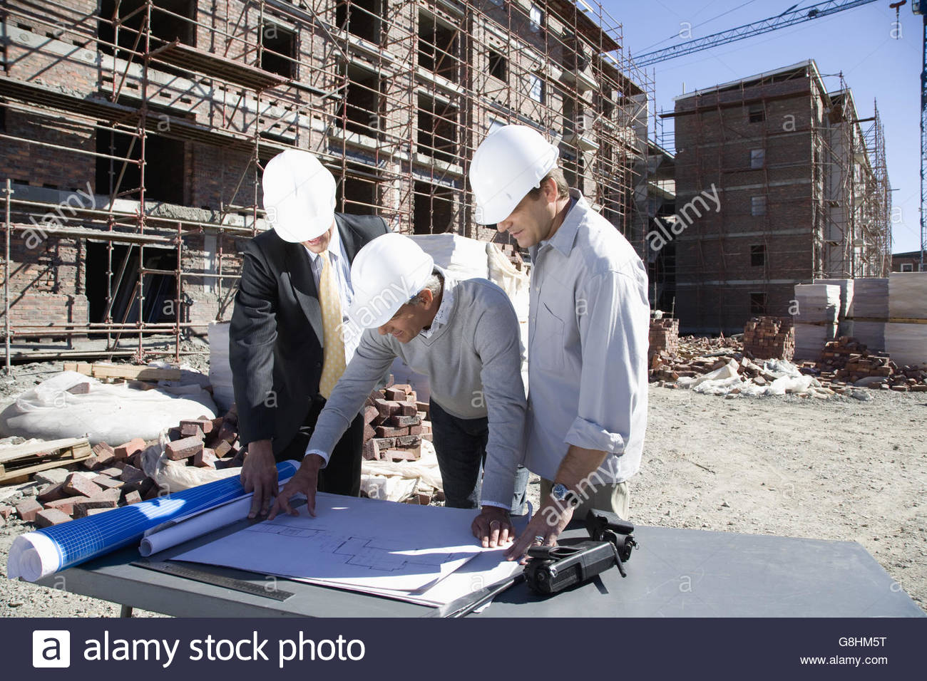 Foreman and co workers looking at blueprints on construction site foreman and co workers looking at blueprints on construction site malvernweather Image collections