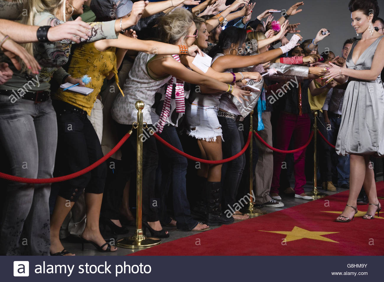 Celebrity signing autograph for screaming fans - Stock Image