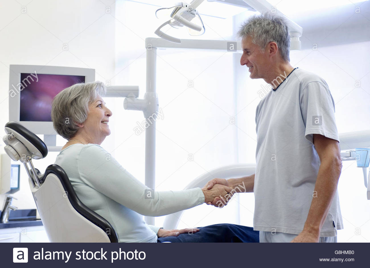 Patient sitting in dentist's chair shaking hands with dentist - Stock Image