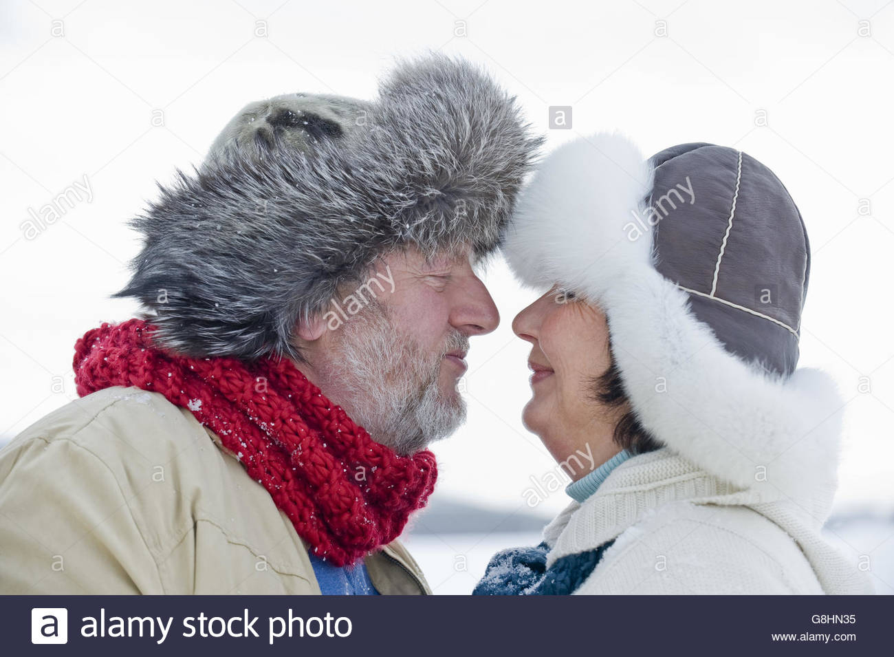 Senior couple in fur-trimmed hats touching noses - Stock Image